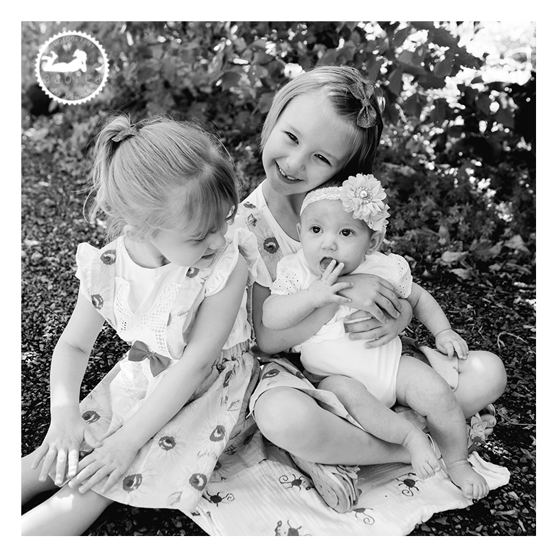 Black and white portrait of three sisters in the gardens behind the Kennewick, WA library. Portrait by Adored by Meghan Rickard Photography in Tri-Cities, WA