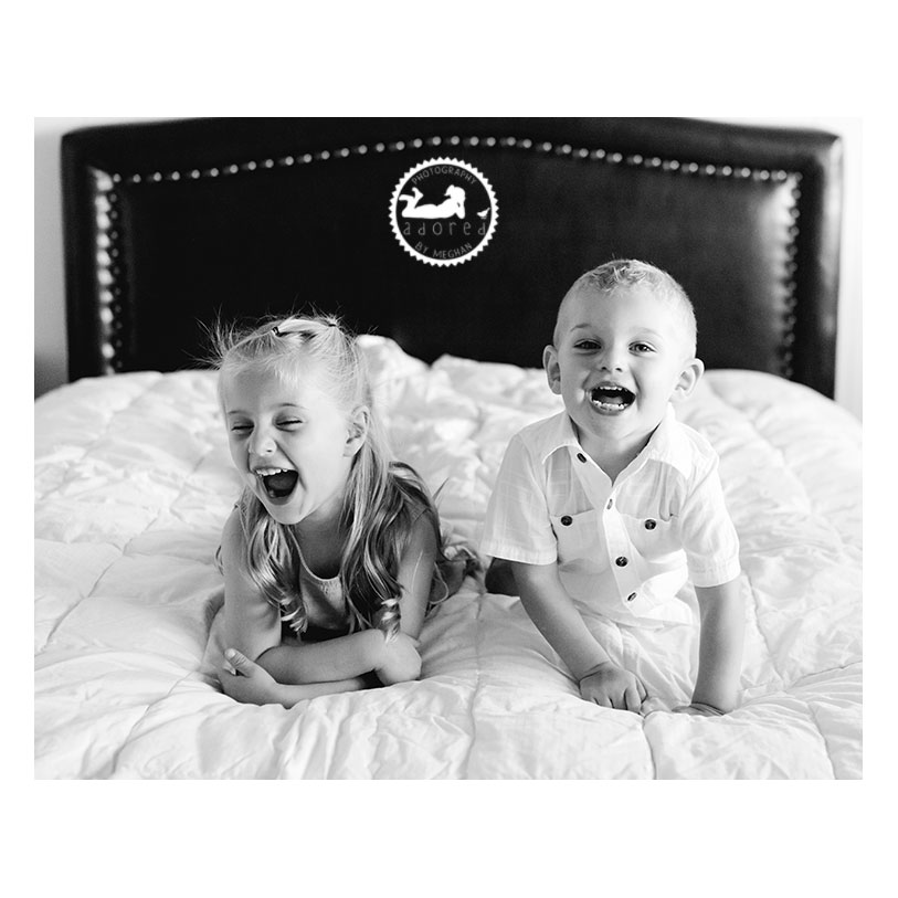 Adored by Meghan Children's Lifestyle Photographer. Siblings laughing on Mom's bed.