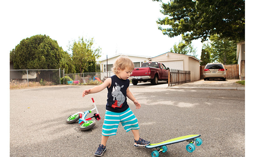 Toddler trying out his birthday choice: skateboard