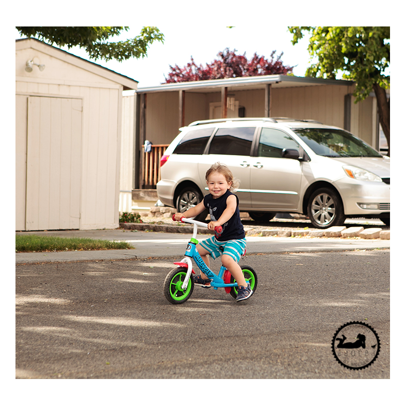 Toddler riding his balance bike on his 3rd birthday